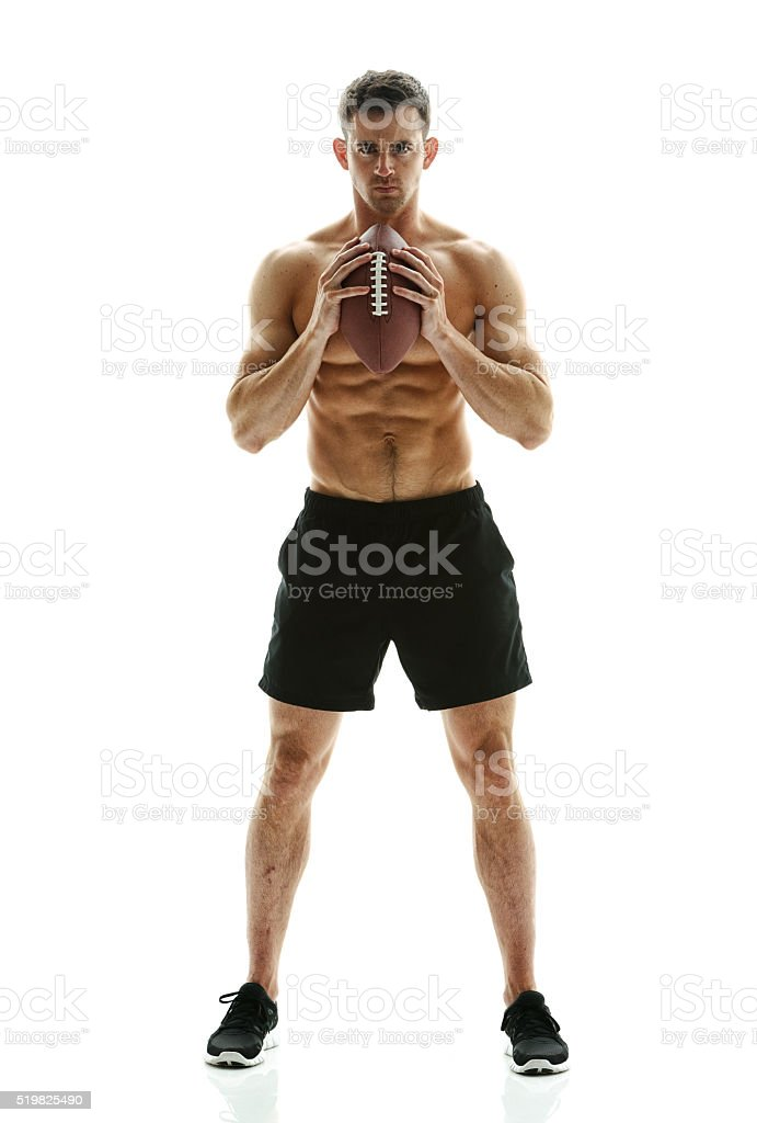 Muscular man posing with football stock photo
