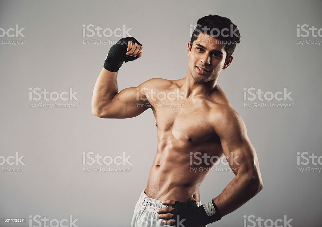 Muscular man pulling his bicep to show off stock photo