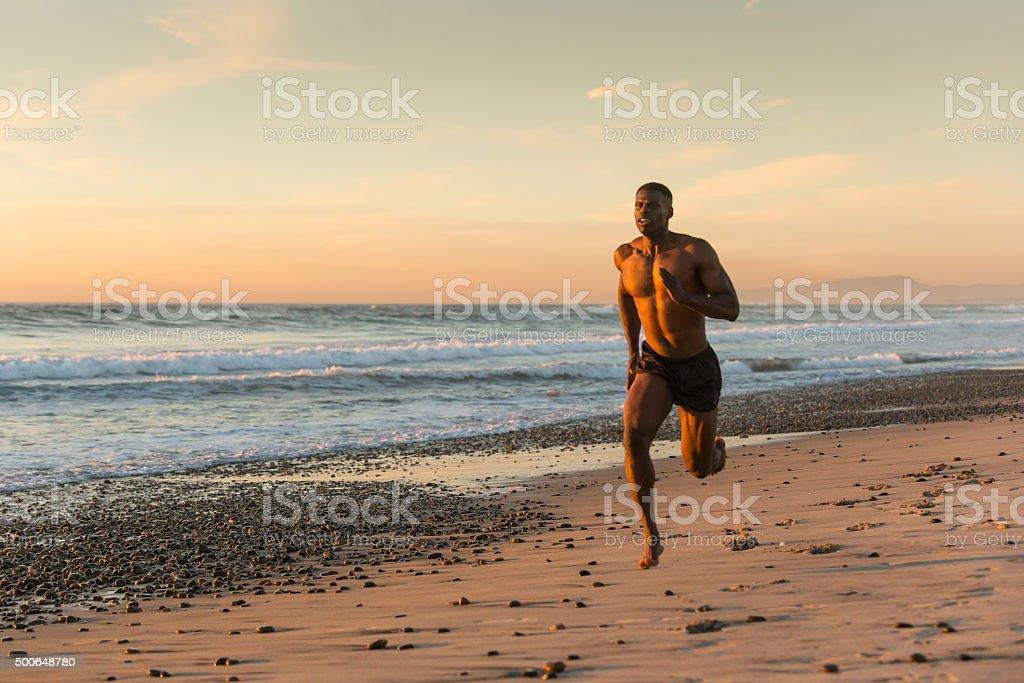 Muscular Man Running On The Beach At Sunset stock photo