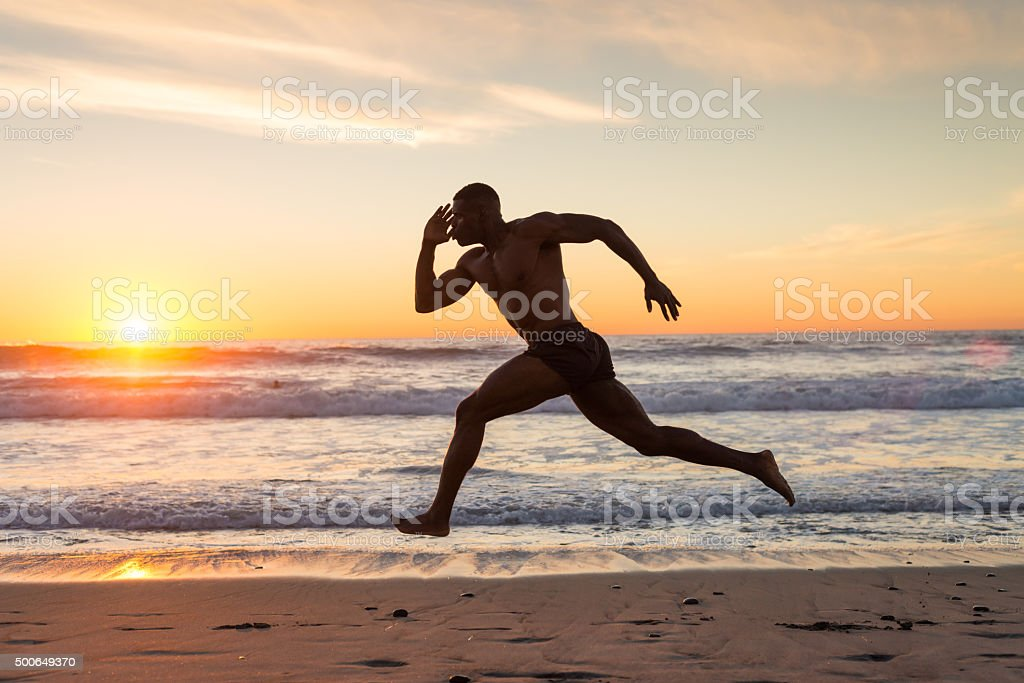 Muscular Man Running On The Beach At Sunset stock photo