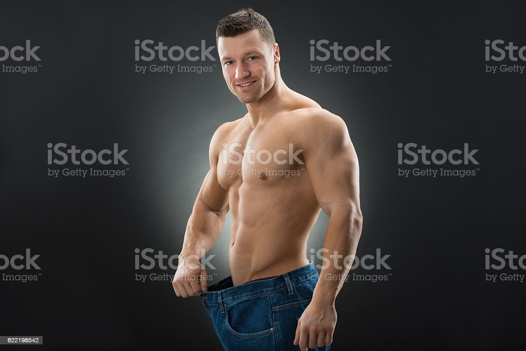 Muscular Man Showing Weight Loss By Wearing Old Jeans stock photo