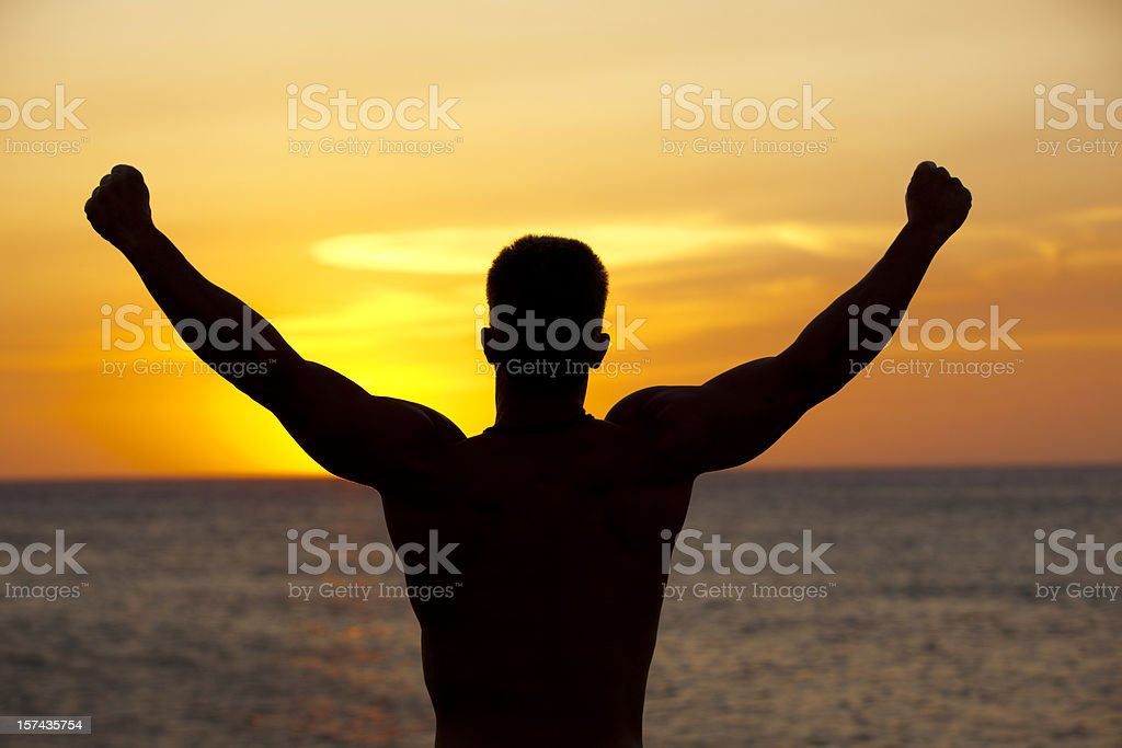 Muscular man silhouetted against sunset royalty-free stock photo