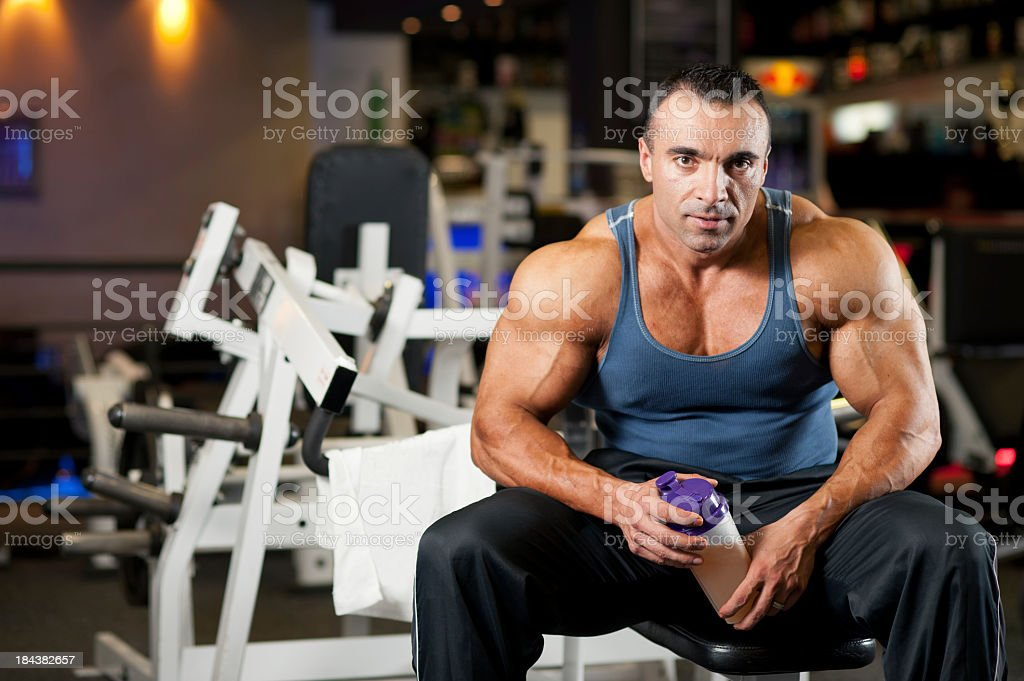 A muscular man sitting in the gym stock photo