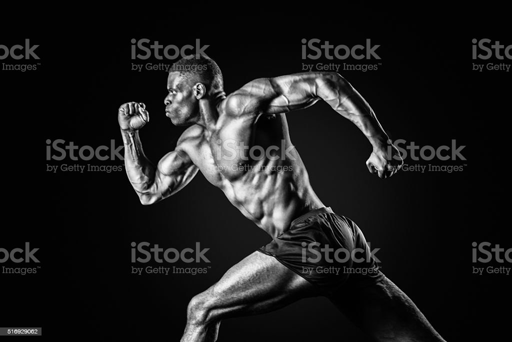 Muscular Man Sprinting On A Black Background stock photo