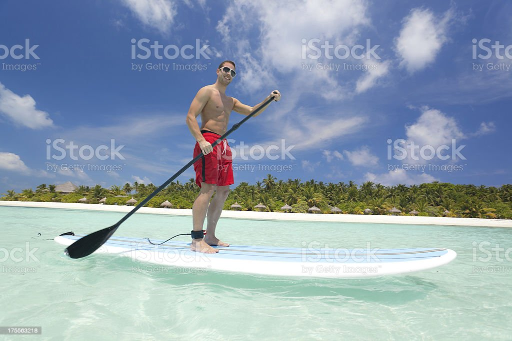 muscular man stand up paddling royalty-free stock photo