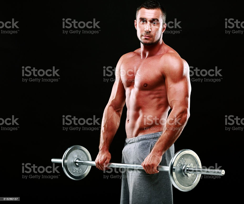 Muscular man standing with barbell stock photo