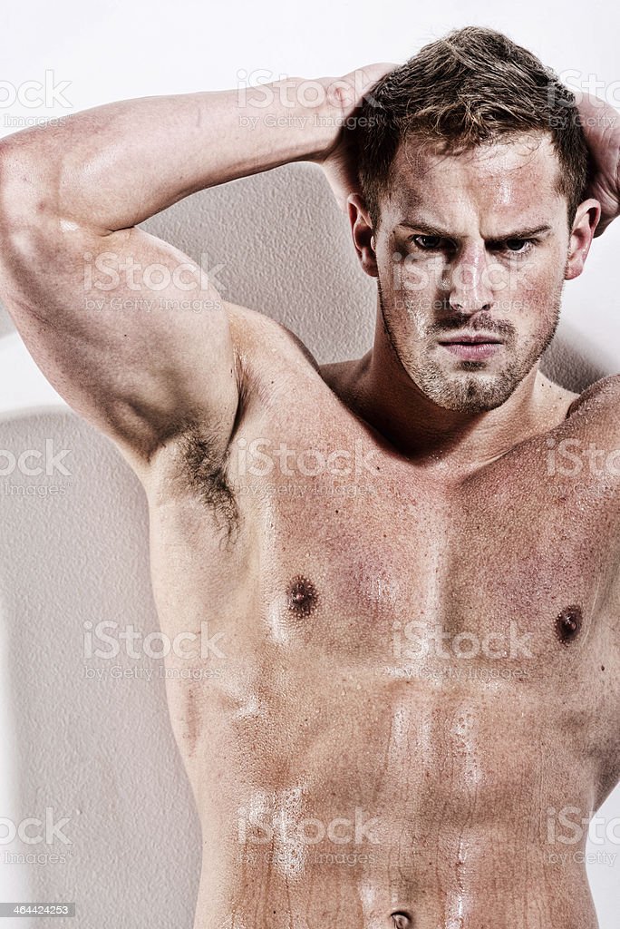 Muscular man standing with hand behind head royalty-free stock photo