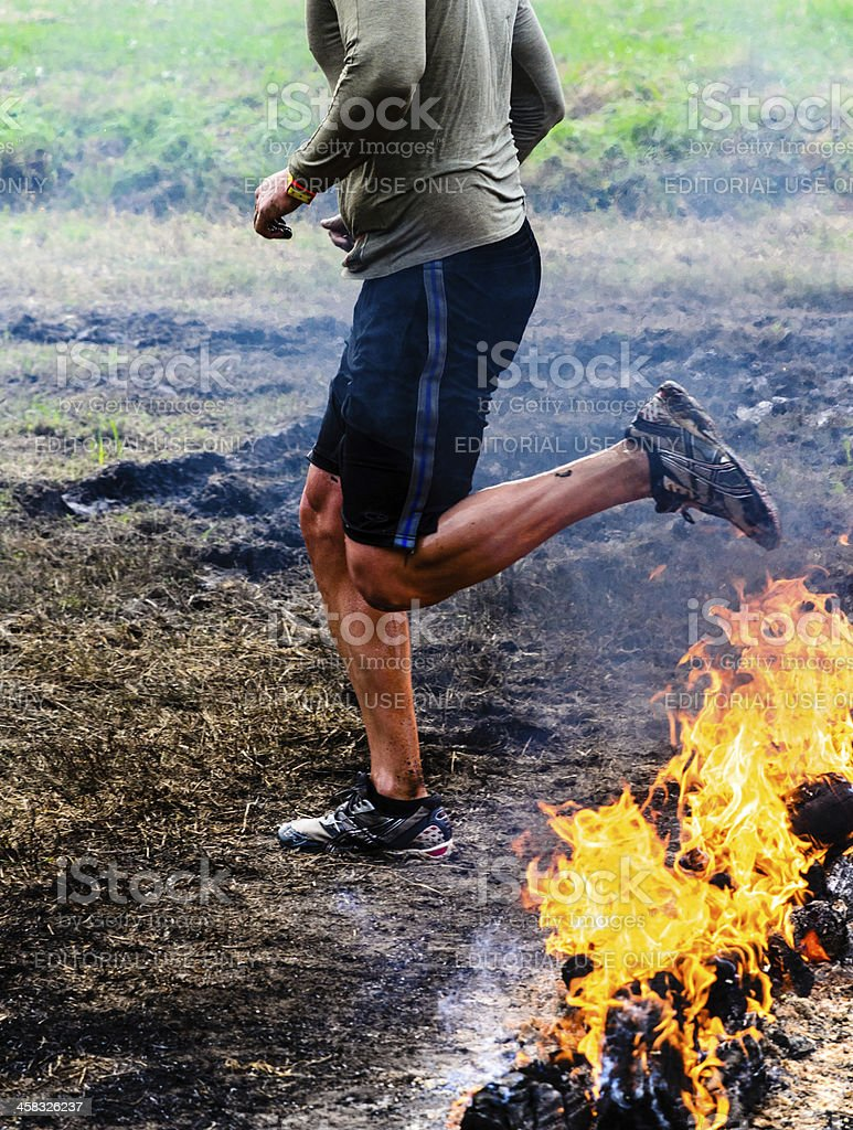 Muscular man stepping over fire stock photo