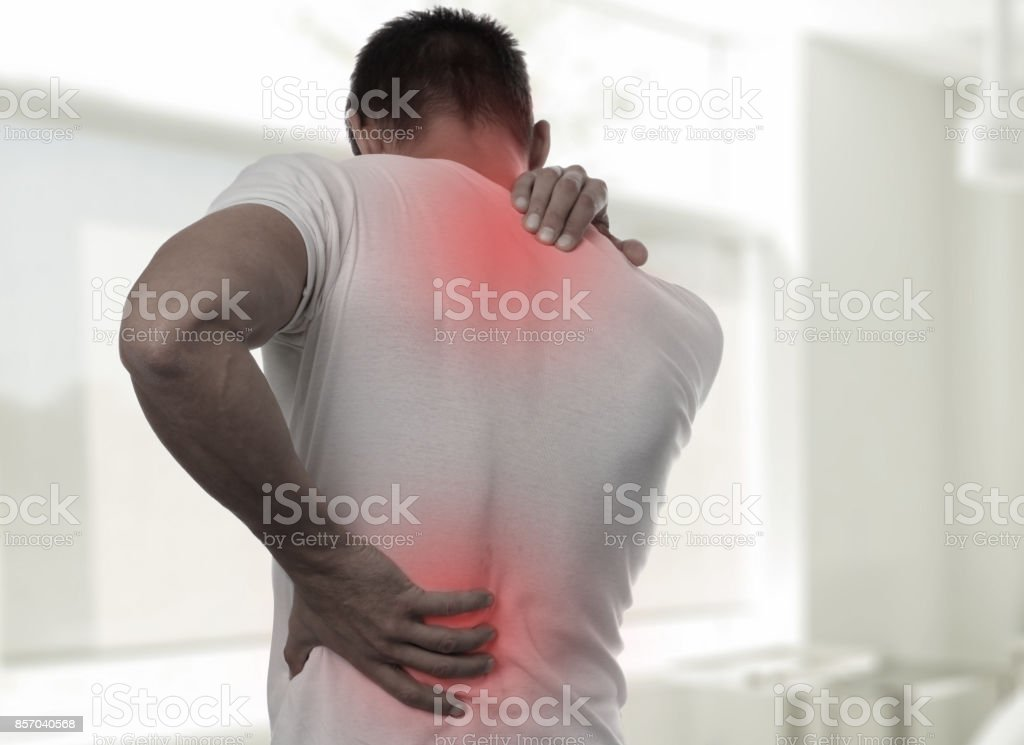 Muscular Man suffering from back and neck pain. Incorrect sitting...