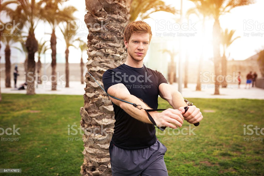 Muscular man training at the park stock photo