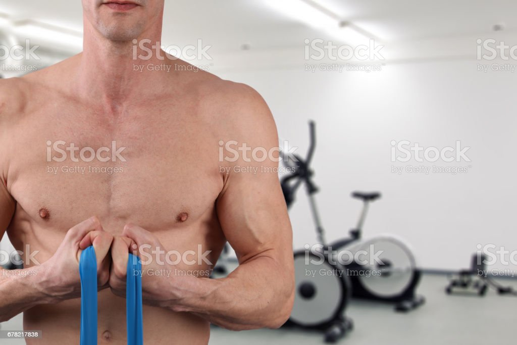 Muscular Man usind elastic band during stretching workout. stock photo