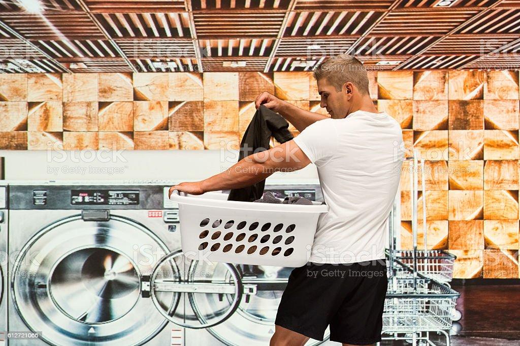 Muscular man washing clothes at laundromat stock photo