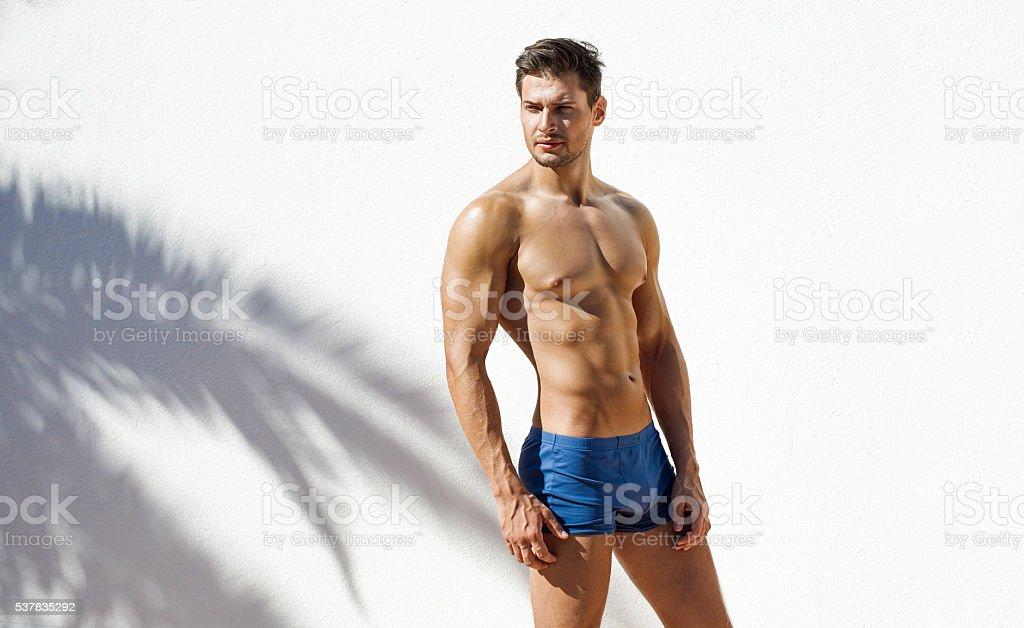 Muscular man wearing blue beach shorts and posing stock photo