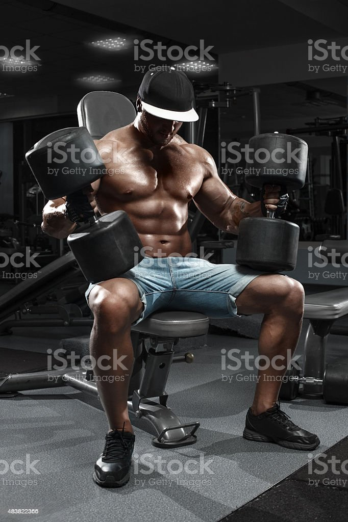 Muscular man with big dumbbells working out in gym stock photo