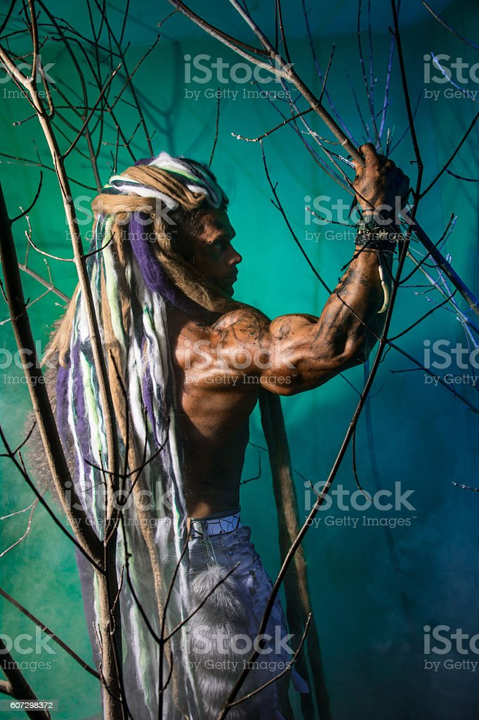 Muscular man with dreadlocks in the forest stock photo