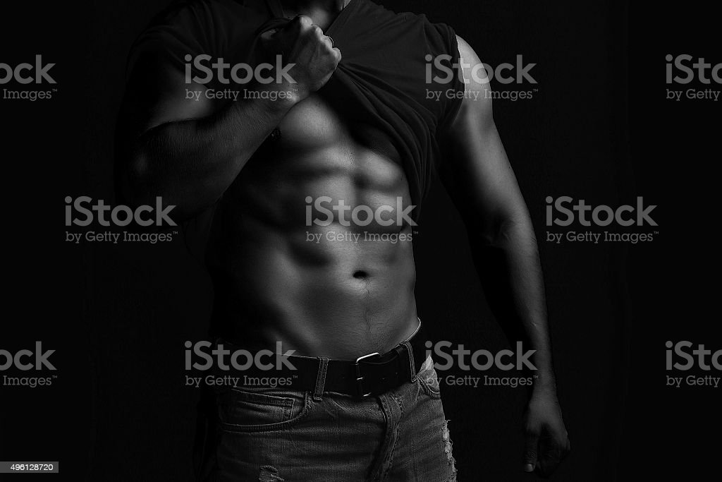 Muscular man with shirt on shoulder stock photo