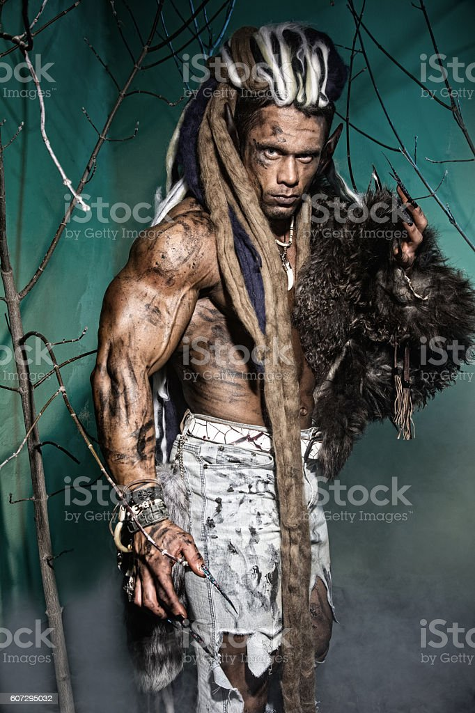Muscular man with skin and dreadlocks among the trees stock photo