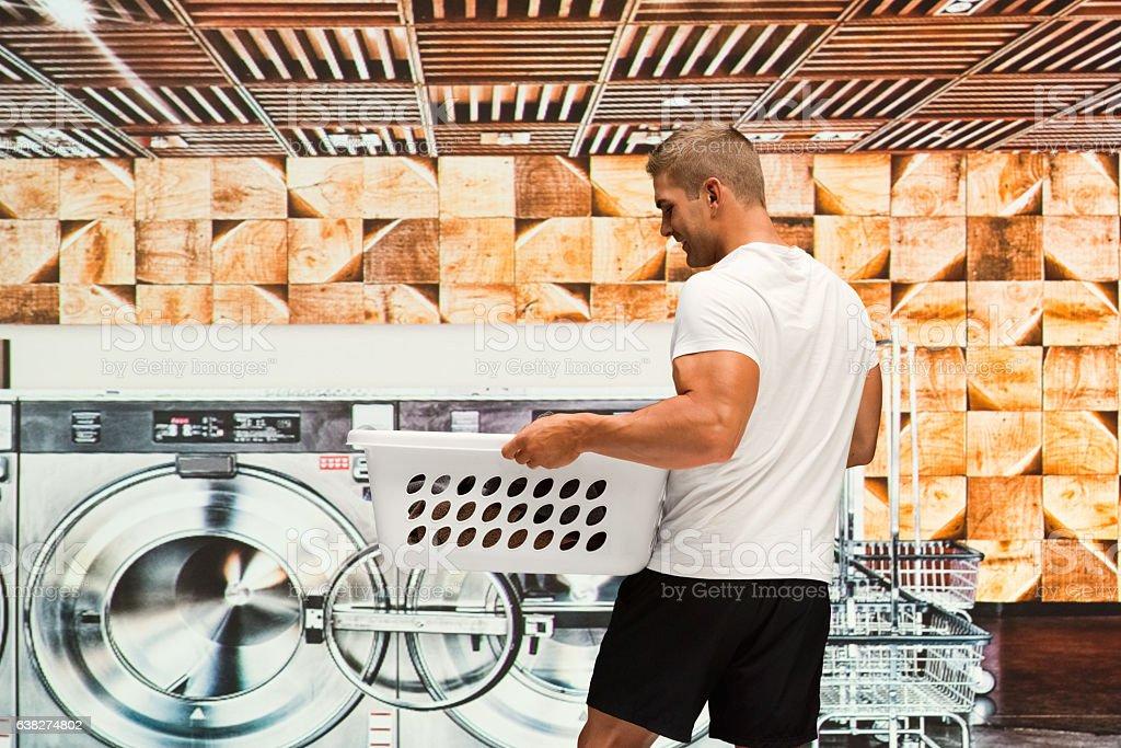 Muscular man working at laundromat stock photo