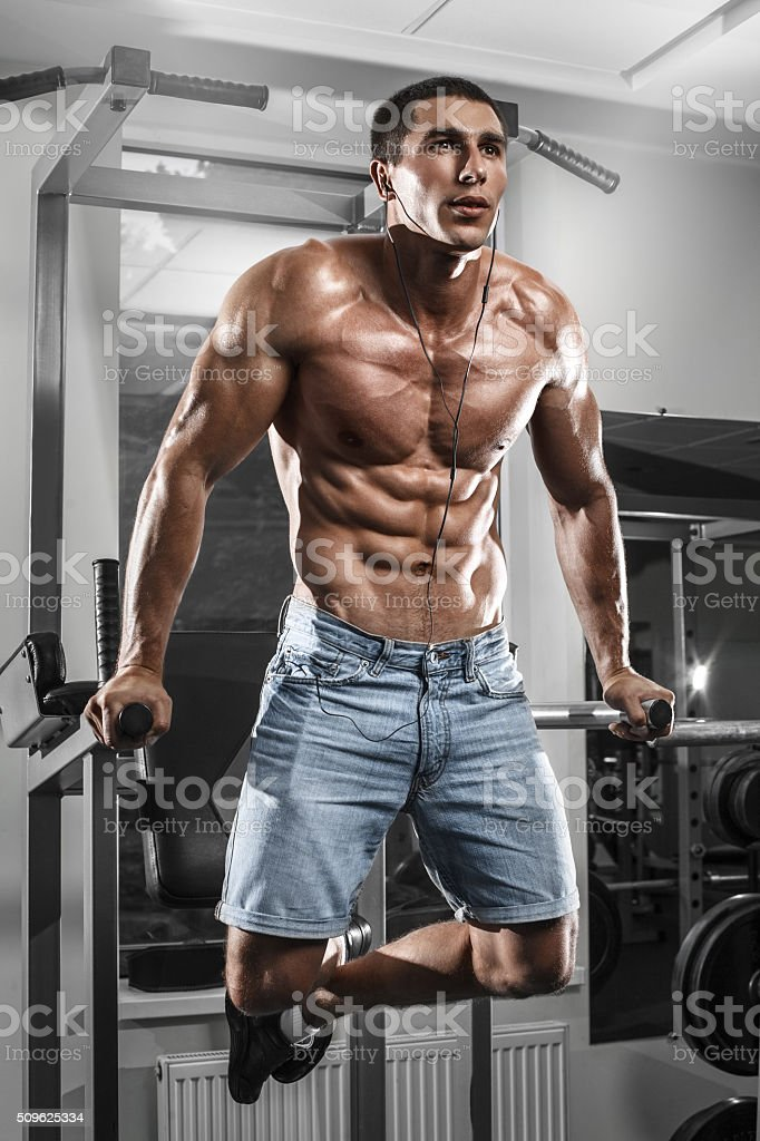 Muscular man working out in gym exercises on parallel bars stock photo