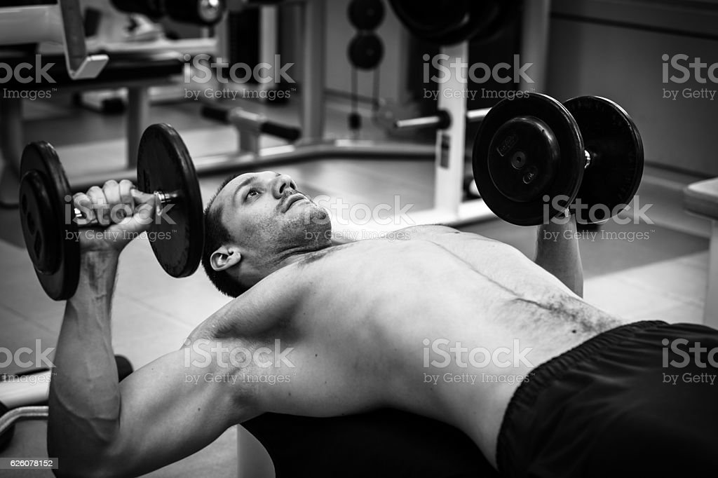 Muscular power athletic male bodybuilder sitting and training stock photo