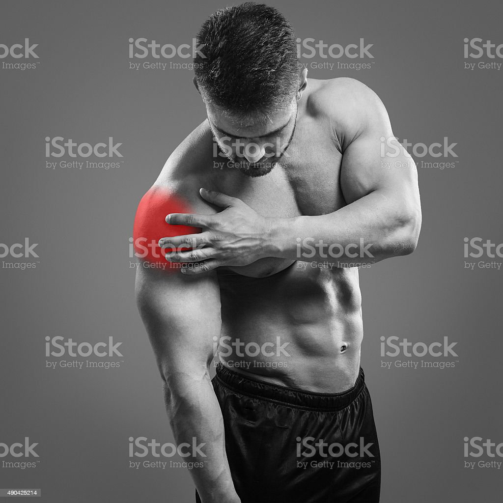 Muscular shirtless man with shoulder pain over gray background. stock photo