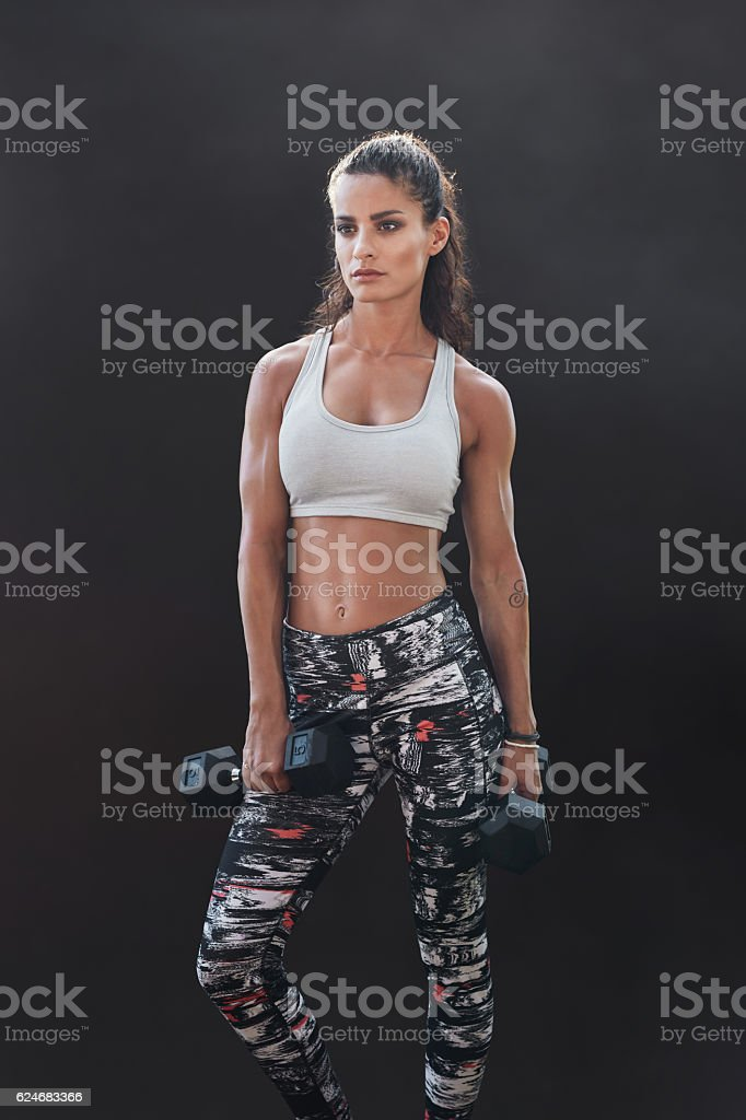 Muscular sportswoman with dumbbells stock photo