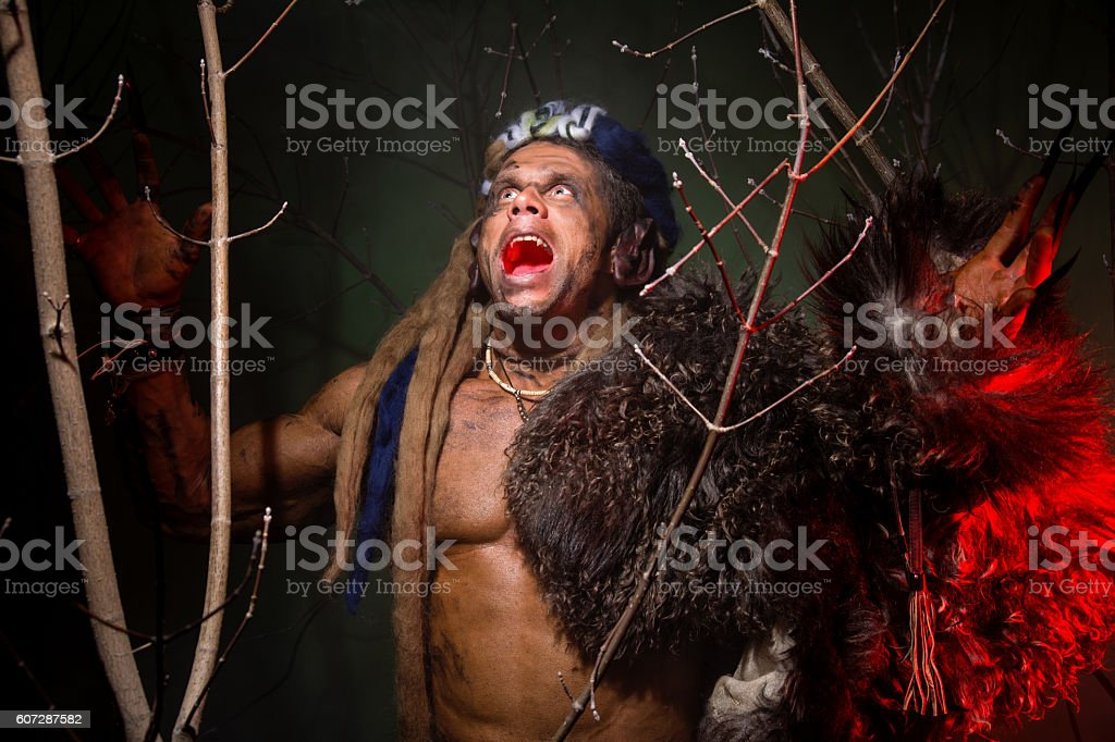 Muscular werewolf hair dreadlocks among the branches of the tree stock photo