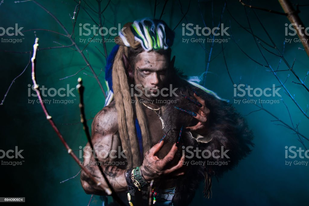 Muscular werewolf with dreadlocks with long nails among the branches of the tree and smoke. stock photo