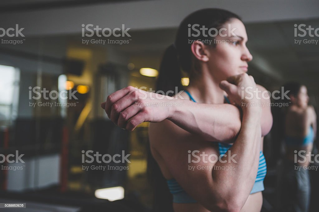 Muscular Woman Doing Arm Stretch stock photo