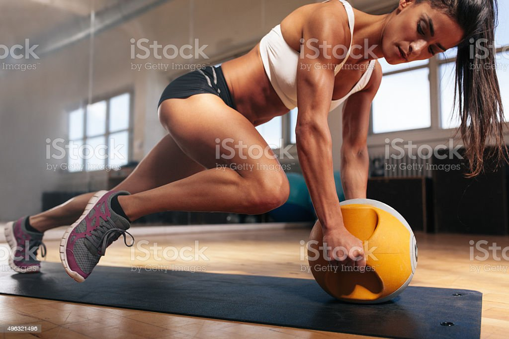 Muscular woman doing intense core workout in gym stock photo