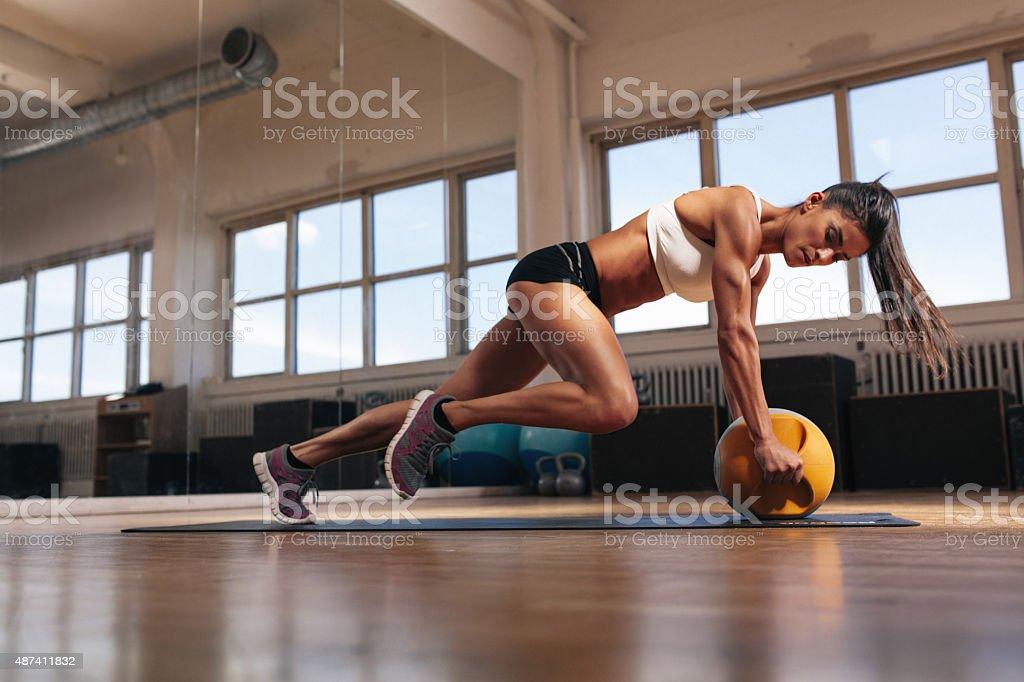 Muscular woman doing intense core workout stock photo