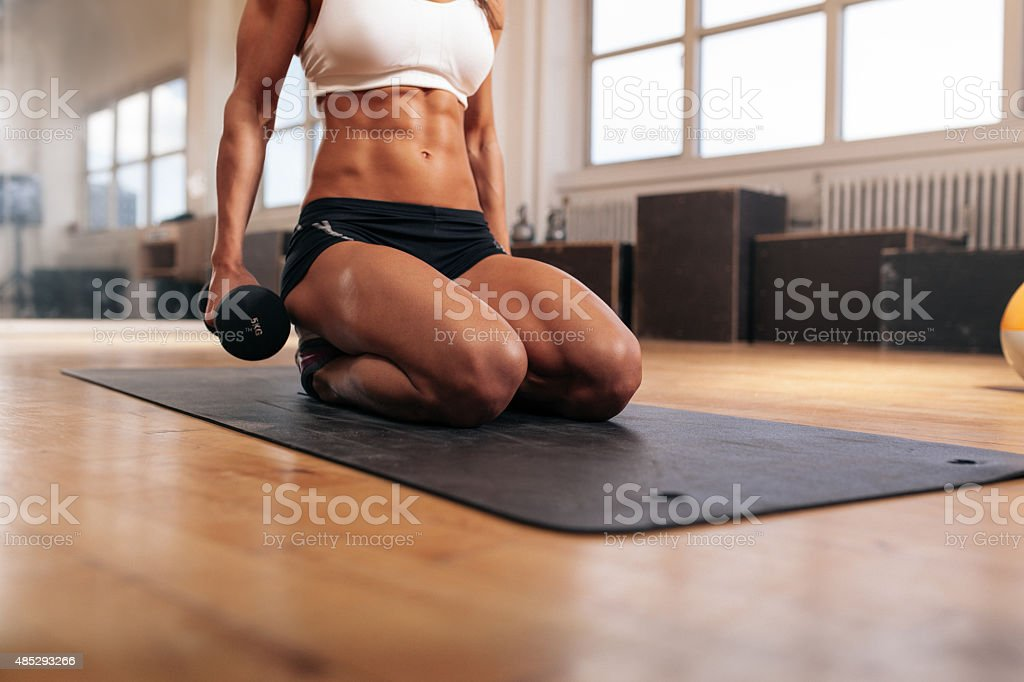 Muscular woman exercising with dumbbells stock photo