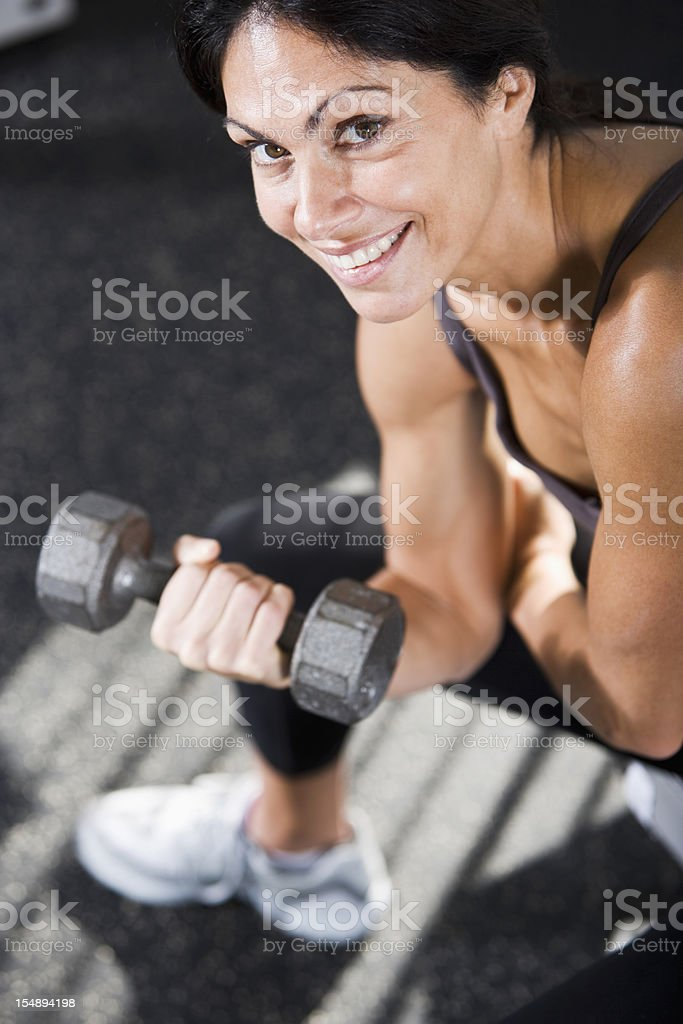 Muscular woman lifting hand weights stock photo