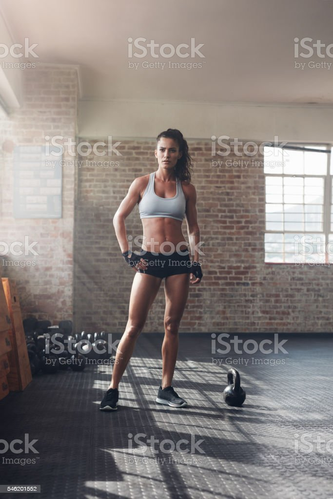 Muscular woman standing in crossfit gym stock photo