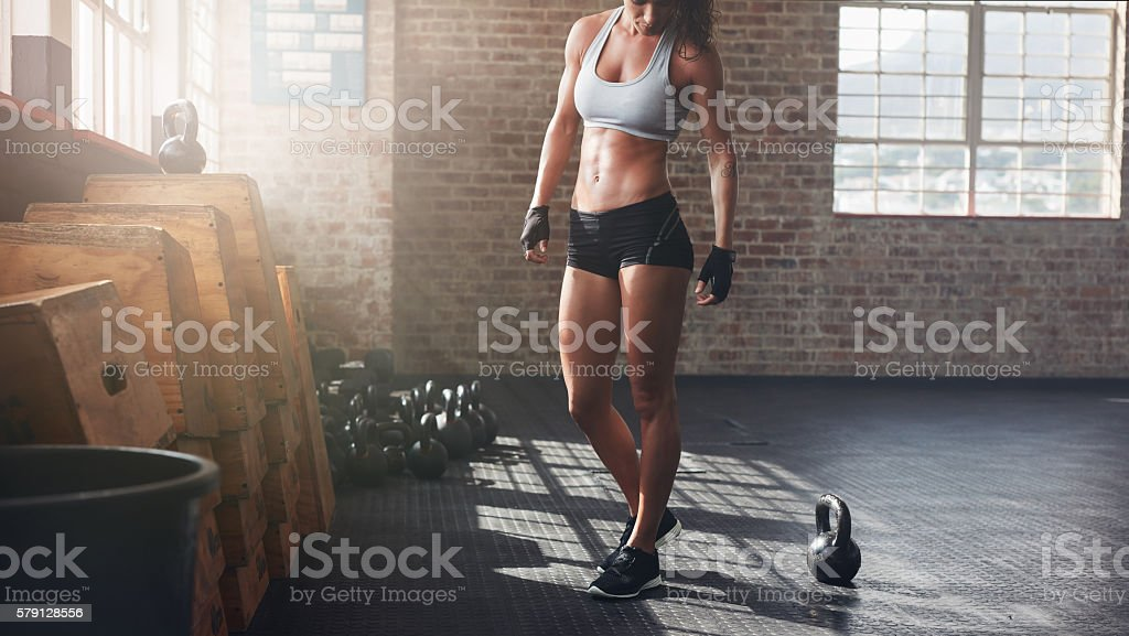 Muscular woman standing in gym stock photo