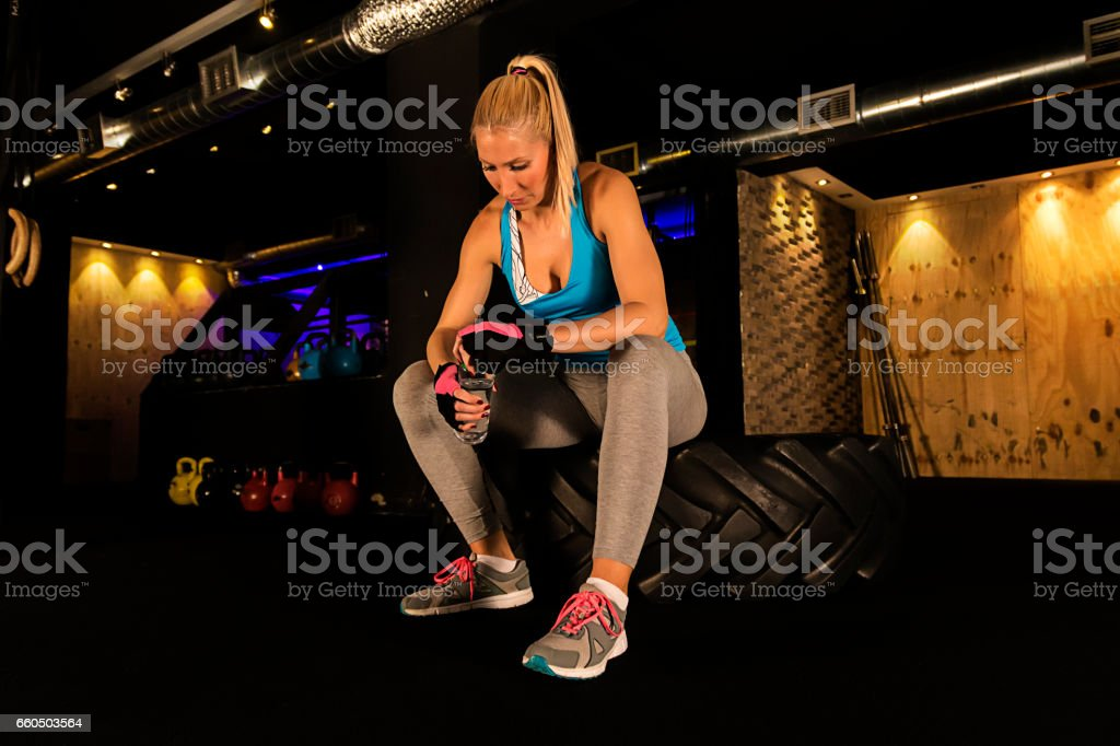 Muscular woman taking break after exercise stock photo