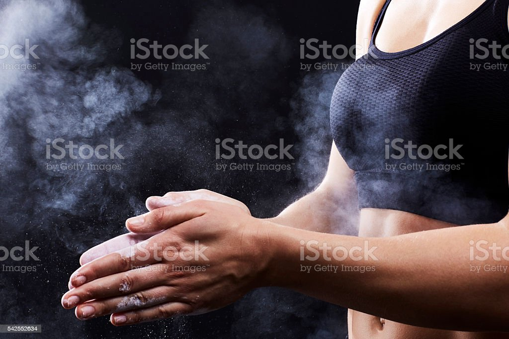 Muscular woman using chalk on hands stock photo