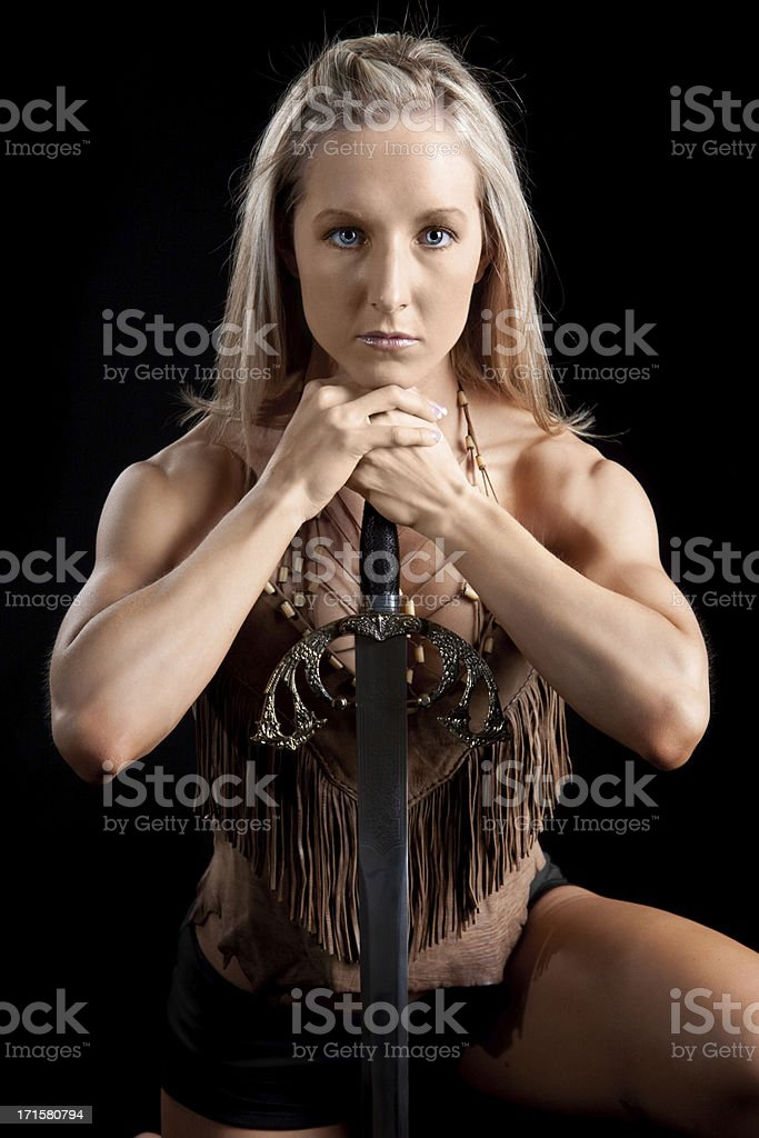Muscular Woman Wearing Leather Leaning on Sword royalty-free stock photo