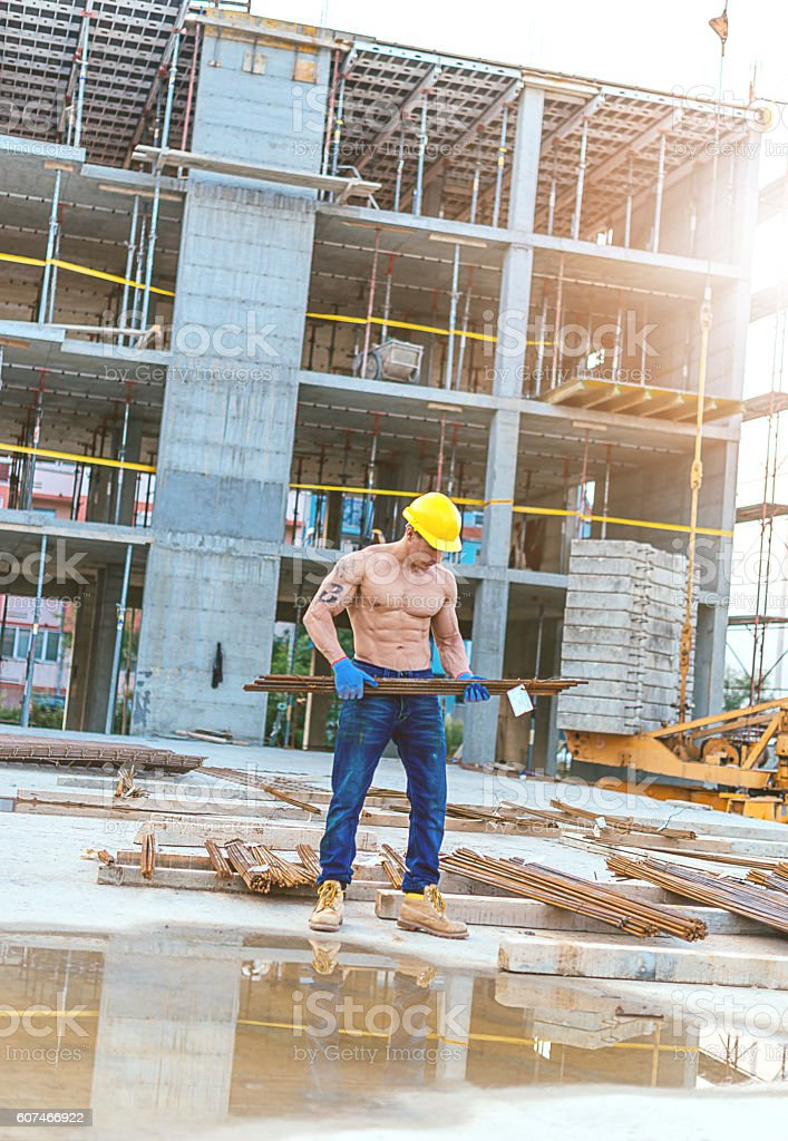 Muscular worker lifting armature and steel rods stock photo