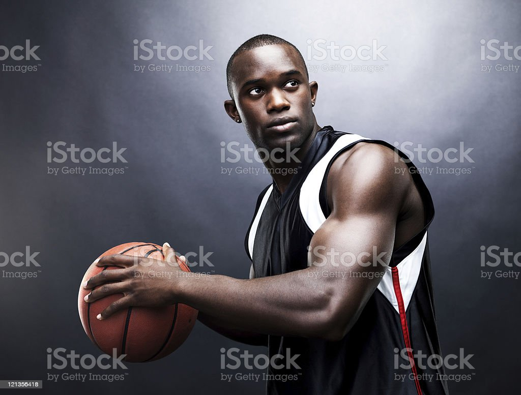 Muscular, young afro-american man playing basketball