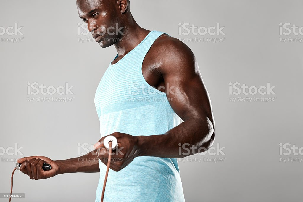 Muscular young man exercising with jumping rope stock photo