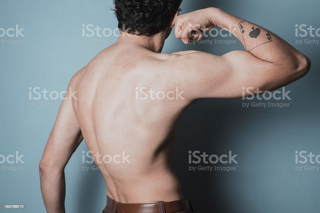 Muscular young man flexing his bicep stock photo