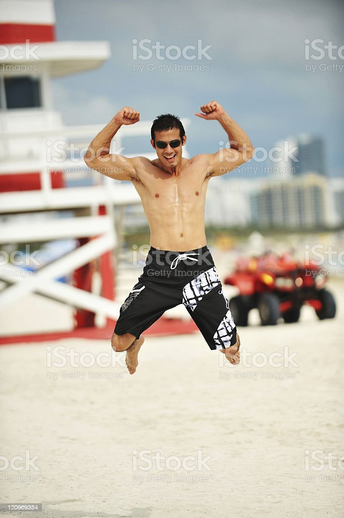 Muscular young man jumps on South Miami Beach royalty-free stock photo