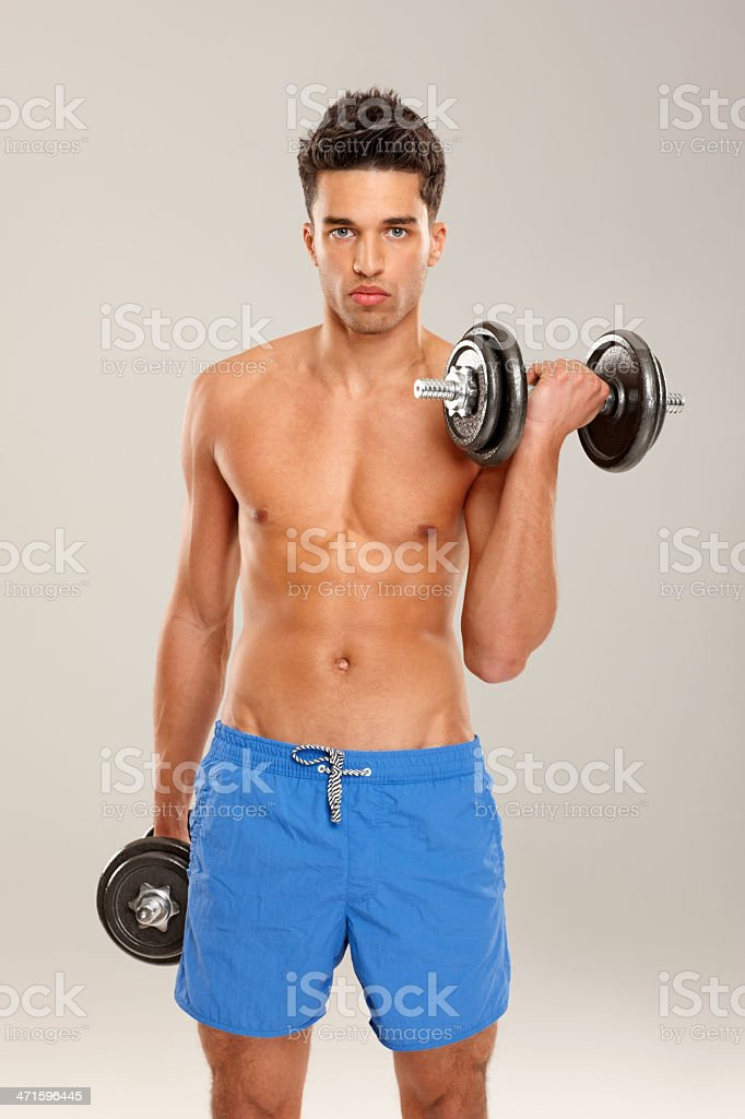 Muscular young man lifting weights royalty-free stock photo