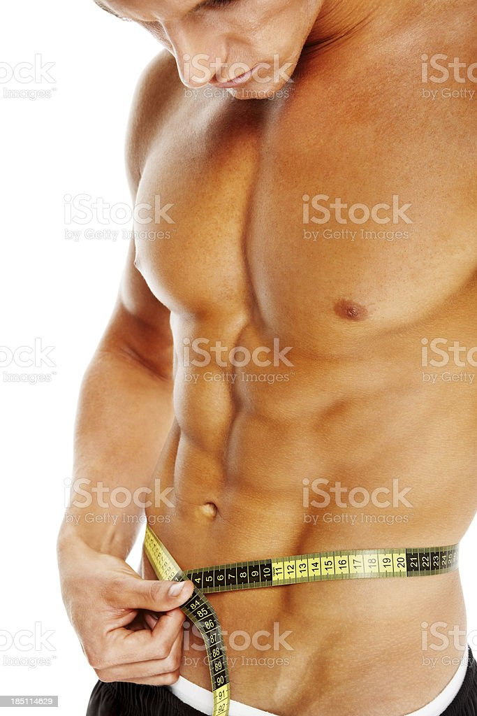 Muscular young man measuring his abs royalty-free stock photo