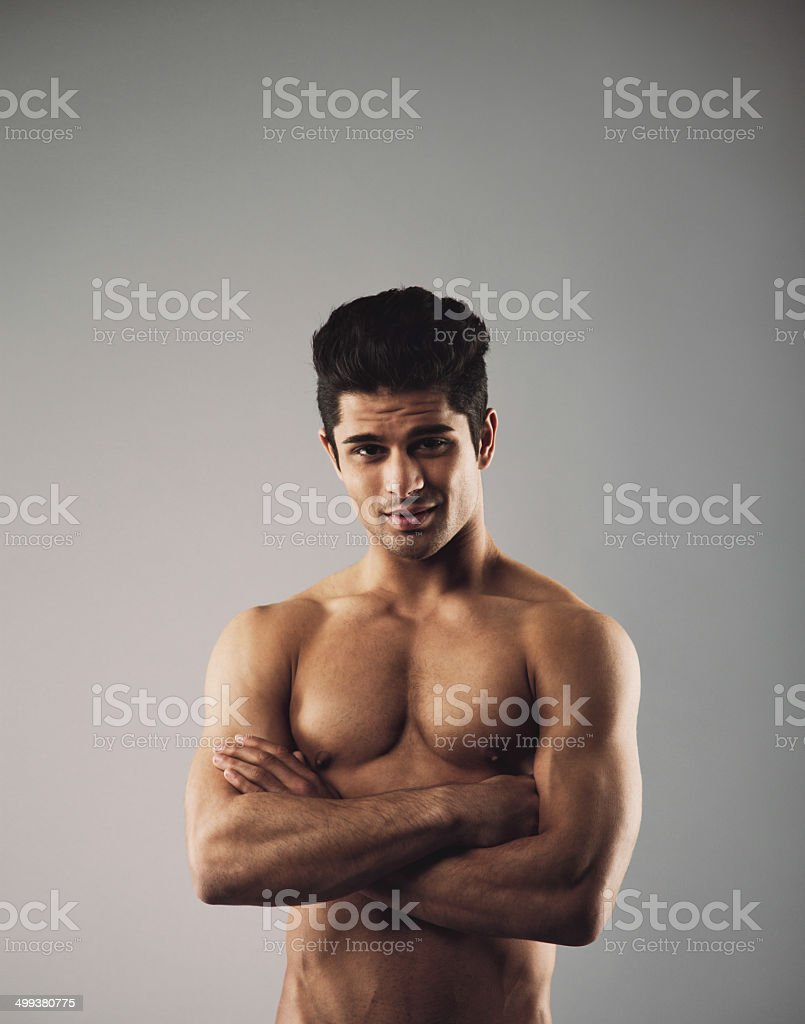 Muscular young man showing off his defined body stock photo