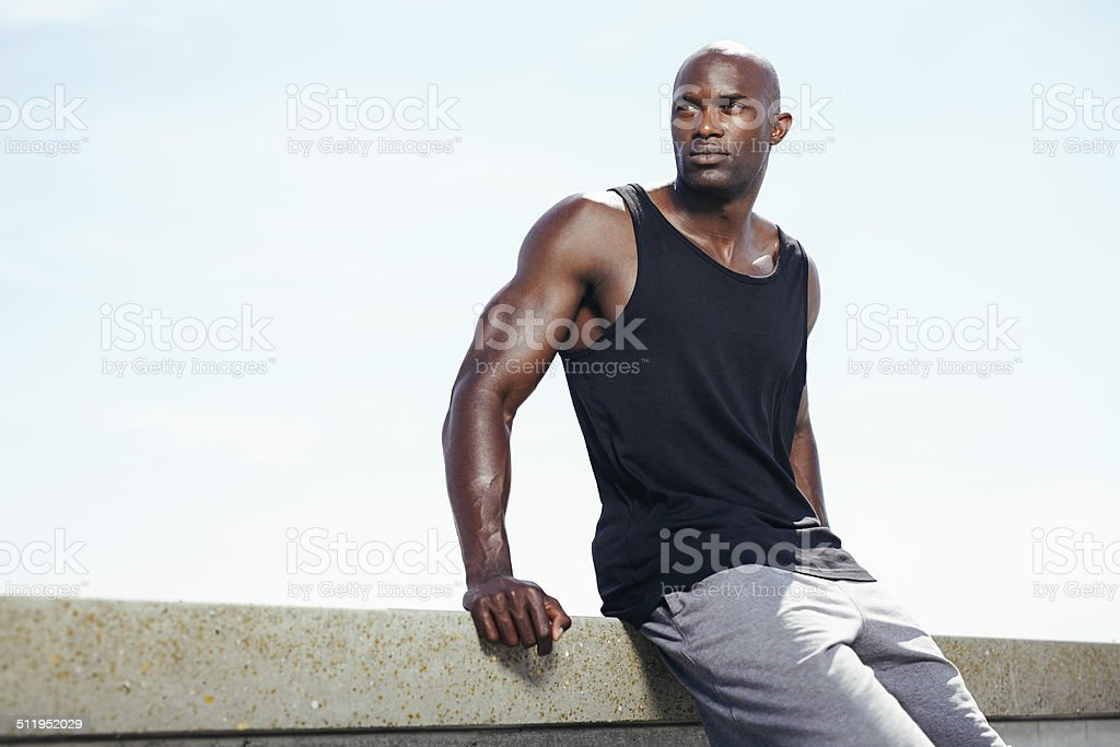 Muscular young man sitting outdoors looking away at copyspace stock photo