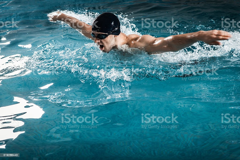Muscular young man swims the butterfly stock photo