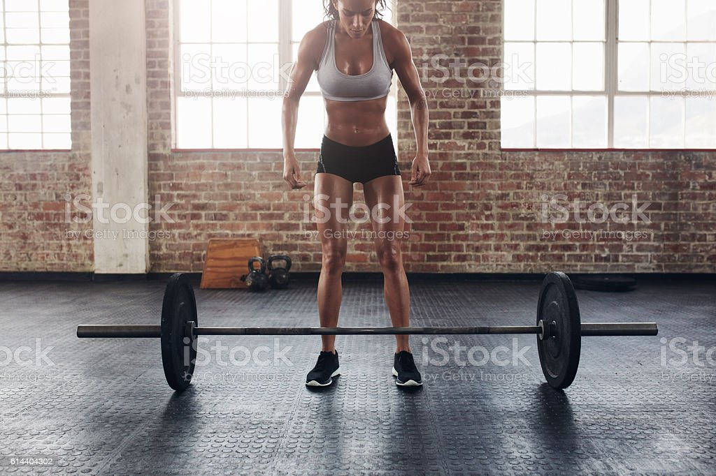Muscular young woman exercising with heavy weights stock photo