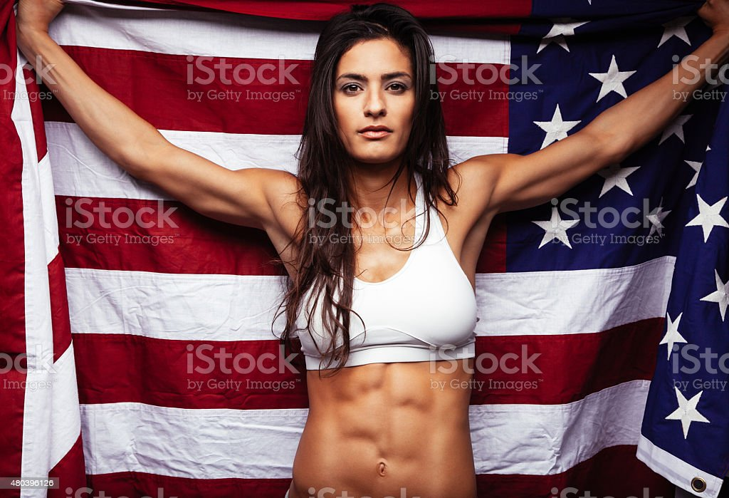 Muscular young woman holding american Flag stock photo